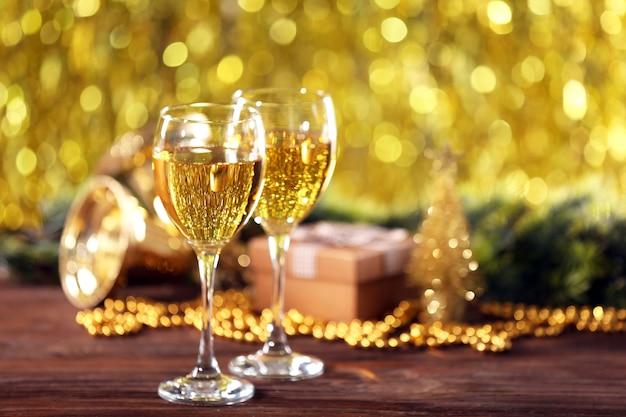 Шампанское и рождественские украшения на ярком фоне