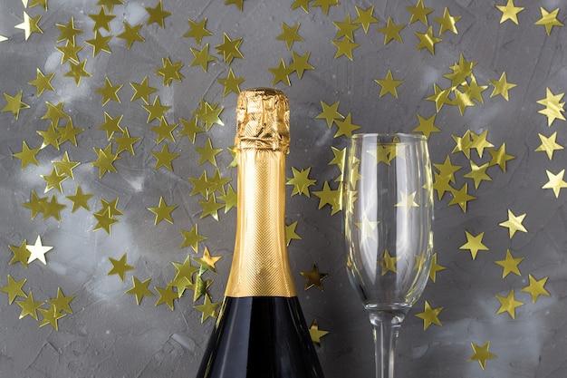 Бутылка шампанского и бокалы с золотыми звездами конфетти. концепция на рождество, новый год, день рождения или свадьбу
