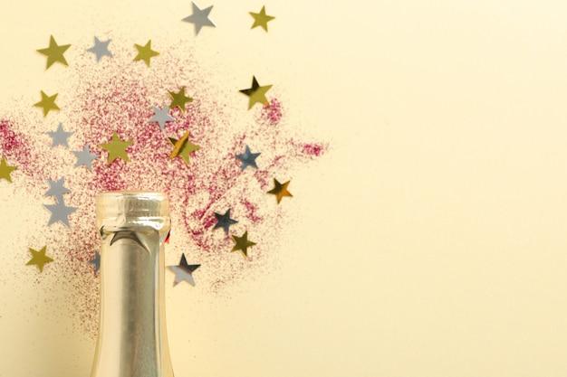 シャンパンのボトルとベージュのキラキラ、クローズアップ