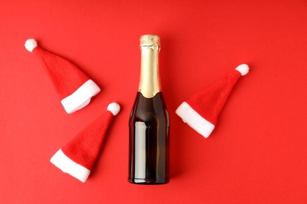 赤の背景にシャンパンボトルとサンタの帽子。