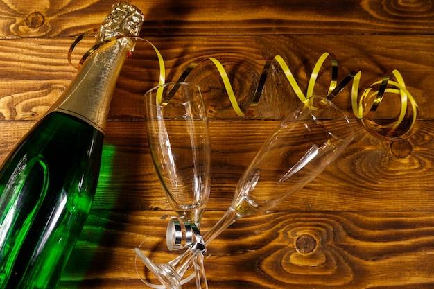 Бутылка шампанского и два пустых бокала для шампанского на деревянных фоне. вид сверху