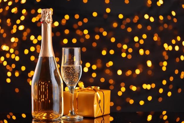 シャンパンボトルとぼやけたクリスマスライトのラップされたギフト