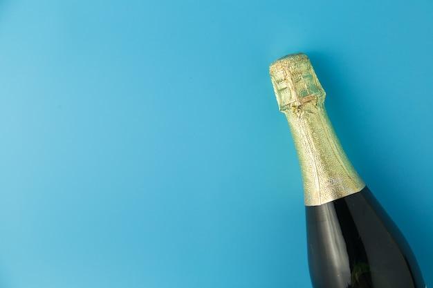 Champagne bottle on blue background, celebration concept.