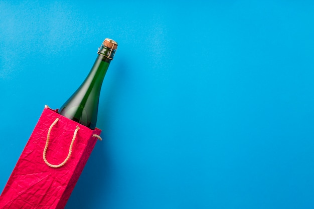 Champagne bottle in bright red paper bag on blue surface