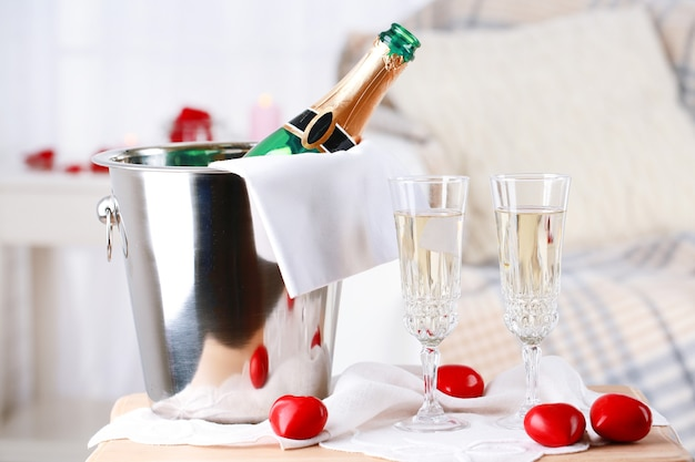 Champagne bottle in bucket,  glasses and rose petals for celebrating valentines day