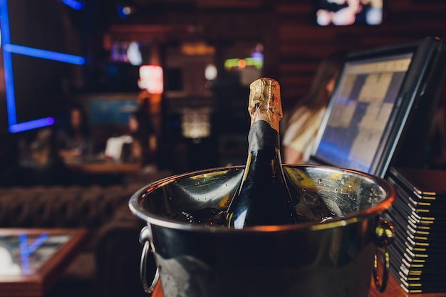 Champagne bottle in a bucket with ice on the dark.