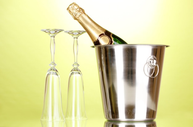 Champagne bottle in bucket with ice and glasses on green background