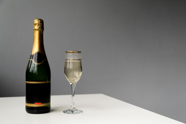 Champagne bottle and champagne glass on white table