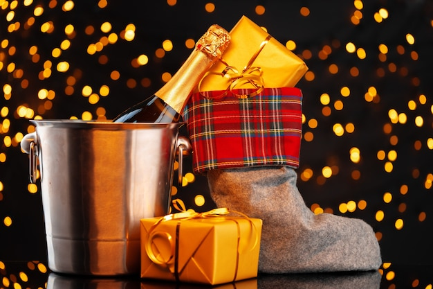 Champagne bottle and christmas stocking with gifts against garland