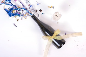 Champagne bottledecorated with confetti and ribbon