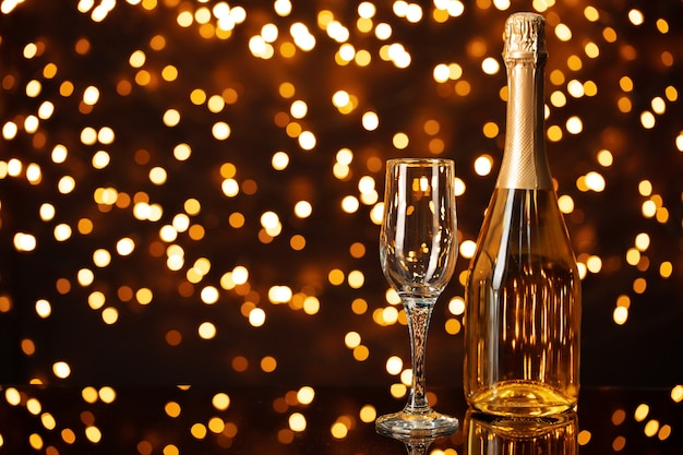 Champagne bottle and glass against shiny bokeh lights background
