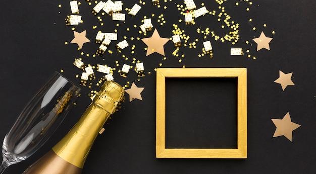 Bottiglia di champagne e vetro accanto al telaio
