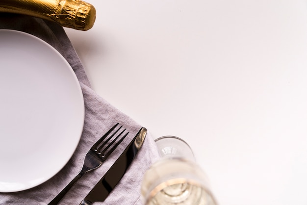 Champagne bottle and glass with empty plate on white backdrop