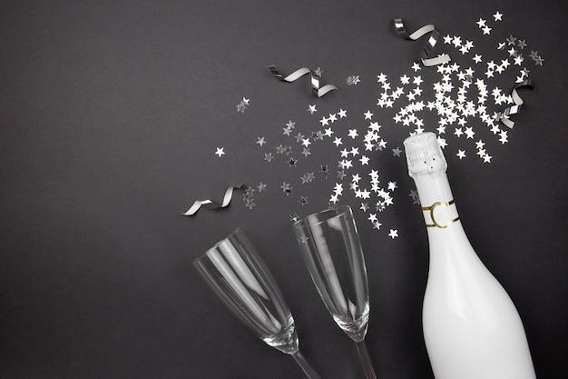 暗い背景にシャンパンボトル、グラス、紙吹雪。お祝いの構成のフラットレイ。