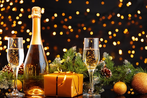 Champagne bottle and glasses on blurred lights background front view
