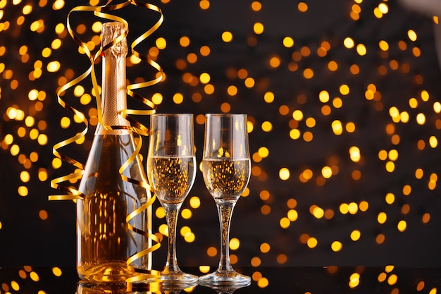 Champagne bottle and glasses on blurred lights background