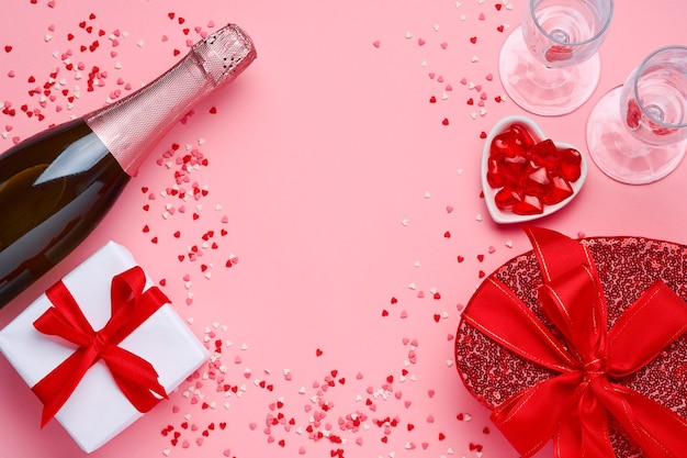 Champagne bottle, glasses and gift box in the form of heart with a red ribbon on pink table. valentines day concept top view.