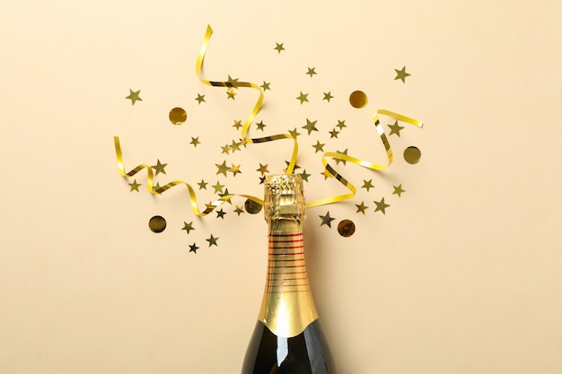 Champagne bottle and glitter on beige, space for text