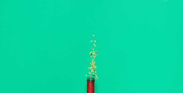 Champagne bottle and golden stars glitter on green