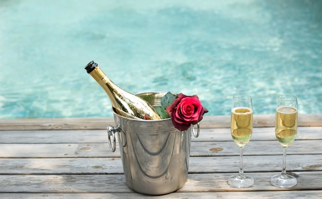 Champagne bottle in ice bucket and champagne glass by swimming pool