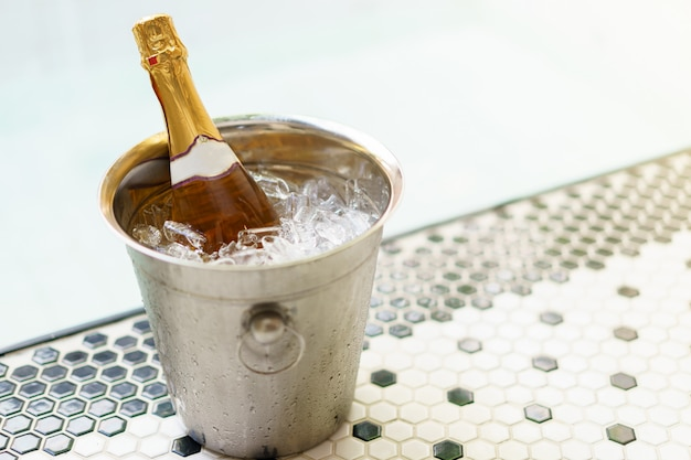 Champagne bottle in ice bucket and two glasses near bubble pool