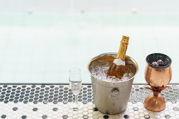 Champagne bottle in ice bucket and two glasses near jacuzzi pool.