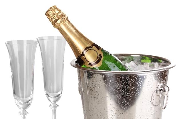 白い表面に分離された氷とグラスとバケツのシャンパンボトル