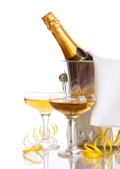 白で隔離の氷とシャンパングラスとバケツのシャンパンボトル