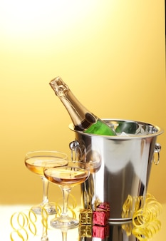 黄色の表面に氷とシャンパンのグラスとバケツのシャンパンボトル