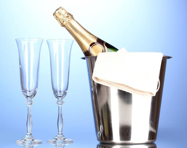 青い表面に氷とグラスとバケツのシャンパンボトル