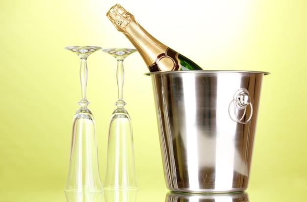 緑の背景に氷とグラスとバケツのシャンパンボトル