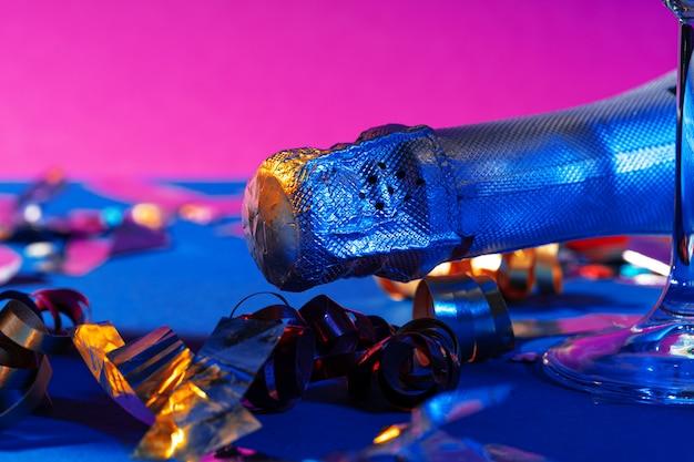 보라색 배경에 샴페인 병을 닫습니다. 파티 컨셉