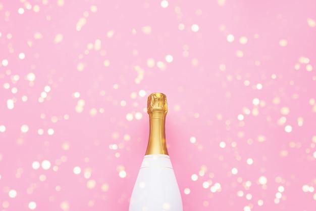 분홍색 배경에 샴페인 병입니다. 크리스마스, 생일, 독신 또는 결혼식 개념. 플랫 레이 스타일. 상위 뷰, 복사 공간.