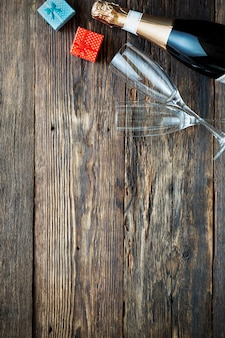 Champagne bottle and two empty glasses on a wooden
