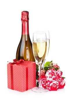 샴페인 병, 두 잔, 선물 상자, 빨간 장미 꽃. 흰색 배경에 고립