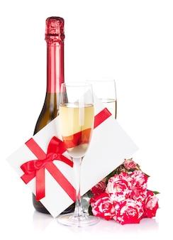 샴페인 병, 두 잔, 편지와 빨간 장미 꽃. 흰색 배경에 고립