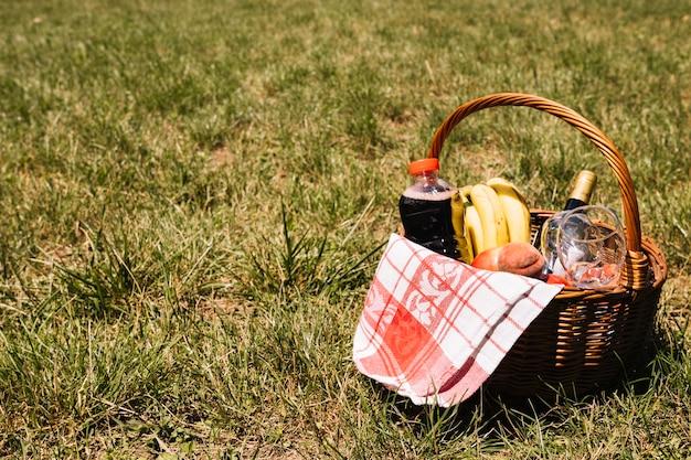 Champagne bottle; wineglasses; juice bottle; fruits and napkin in wicker basket on green grass