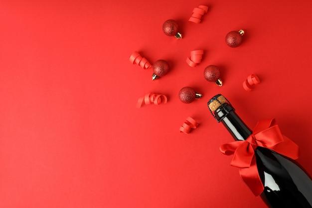 弓と赤い背景のつまらないものとシャンパンボトル。