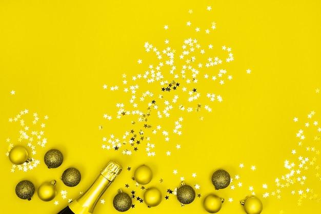 黄色の背景にクリスマスの装飾が施されたシャンパンボトル。上面図、コピースペース