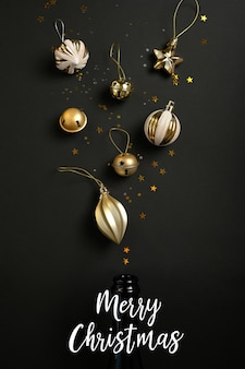 Champagne bottle with different christmas decoration on black background. open champagne concept. flat lay.