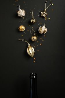Champagne bottle with different christmas decoration on black surface. open champagne concept. flat lay.