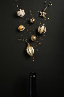 黒い表面に異なるクリスマスの装飾が施されたシャンパンボトル。オープンシャンパンのコンセプト。フラットレイ。