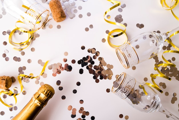 Champagne bottle with empty glasses; confetti and streamers on white background