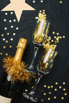 黒のテーブルに眼鏡を持つシャンパンのボトル