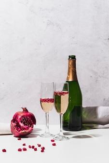 Bottiglia di champagne con bicchieri e melograno