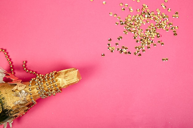 Champagne bottle with golden confetti on pink paper background.