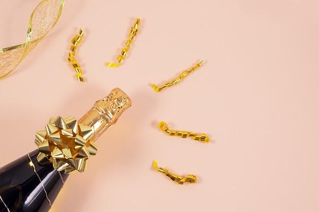 Бутылка шампанского с золотыми лентами и конфетти. празднование нового года