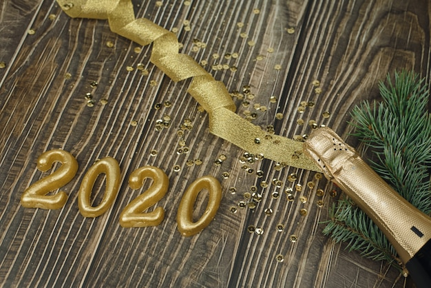 Champagne bottle with golden tinsel, ribbon and confetti and 2020 in numbers