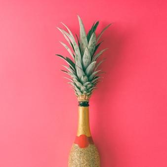 Бутылка шампанского с листьями ананаса на розовой поверхности