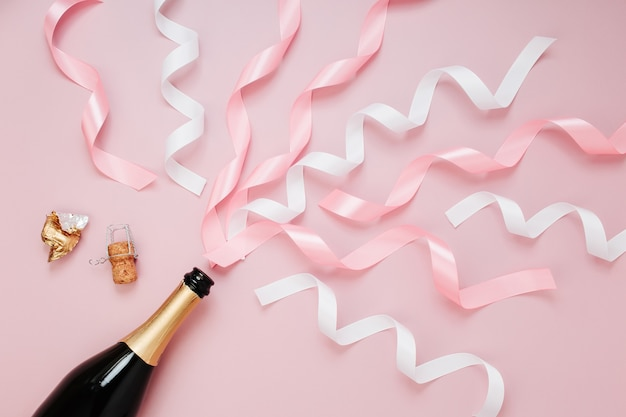 Бутылка шампанского с лентой. плоская планировка, вид сверху модная концепция праздника.